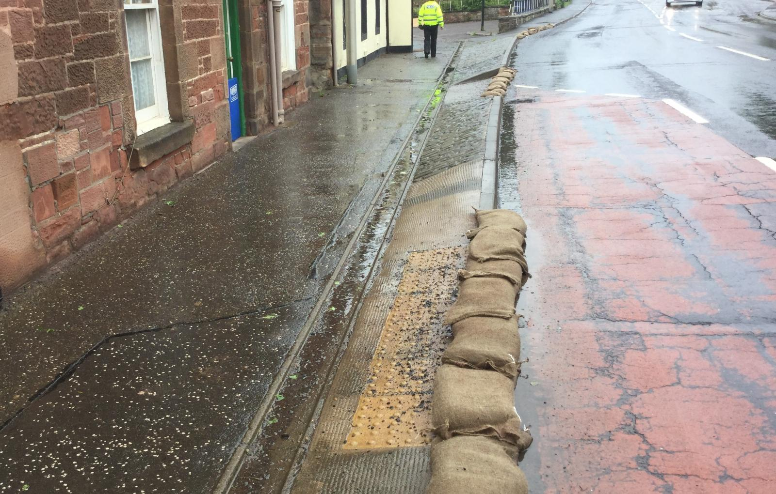 Sandbags and floodgate in use flooded road